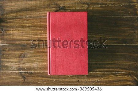 Old vintage red book on the wooden table - stock photo