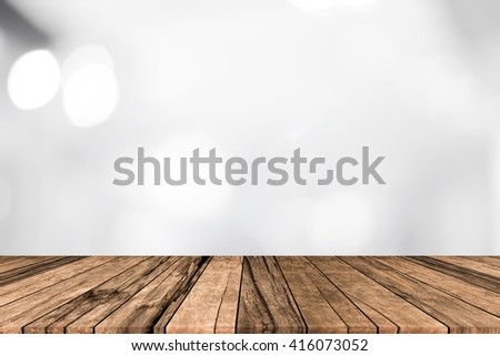 old vintage retro brown wood tabletop with blurred department store mall with bokeh light cool tone background:grunge aged wooden with blurry white color backdrop.showing/advertise product on display - stock photo