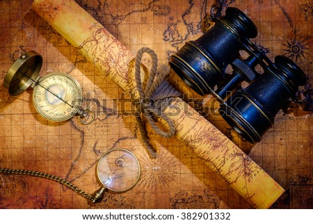 Old vintage retro compass, binoculars and magnifying glass on ancient world map. Vintage still life. Travel geography navigation concept background. - stock photo