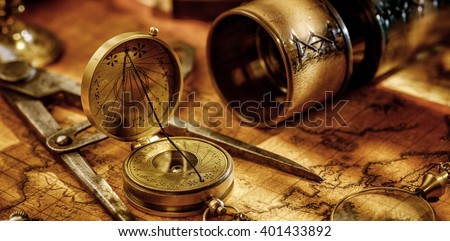 Old vintage retro compass, Spyglass, measuring devices and magnifying glass on ancient world map. Vintage still life. Travel geography navigation concept background.