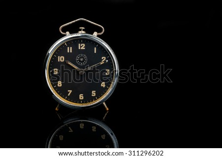 Old vintage round table alarm clock with reflection over black background - stock photo