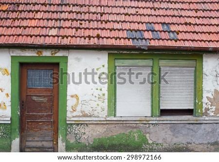 Old vintage rustic German shabby house with peeled white plaster on the wall, wooden door, windows with gray closed horizontal jalousie, roof with red tiles with black patches  - stock photo