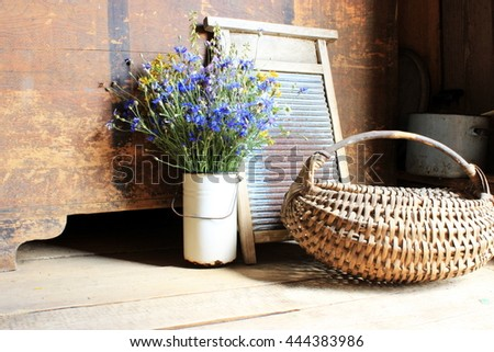 Old vintage rustic interior composed with antique equipment including original household objects: wooden trunk, basket, rusty can with bouquet of blue cornflowers. Countryside. Retro decor