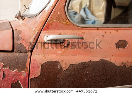 Old vintage rusty car showing detail from the side. - stock photo