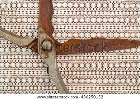 Old vintage rusty scissors on White lace floral pattern textile background, text place - stock photo