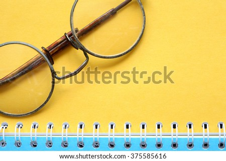 Old vintage spectacles on open notebook with colored pages - stock photo