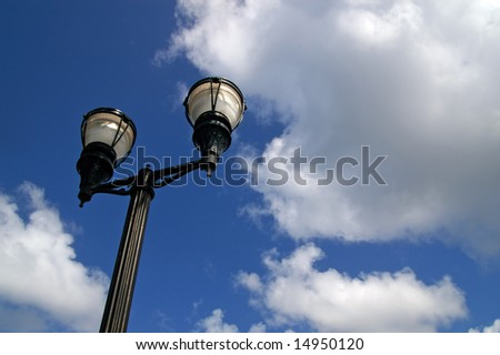 old vintage street lamp against cloudy sky - stock photo