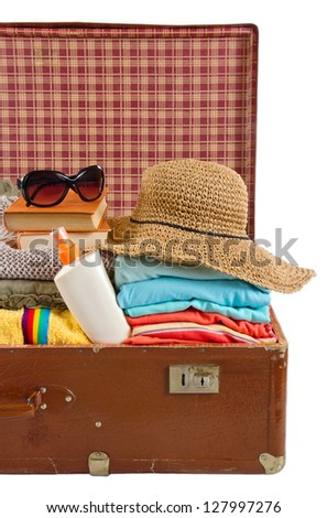 Old vintage suitcase packed with sun hat, clothes, books, sunglasses and beach towel - stock photo