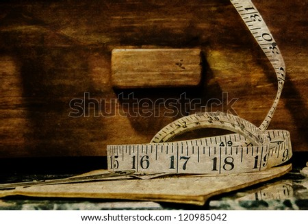 Old vintage tape measure with background of wooden drawer - stock photo
