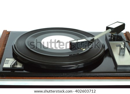 Old vintage three speed turntable in brown wooden case with rotation vinyl record with white label isolated on white background. Horizontal photo front view closeup