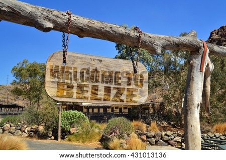 """old vintage wood signboard with text """" welcome to belize"""" hanging on a branch - stock photo"""