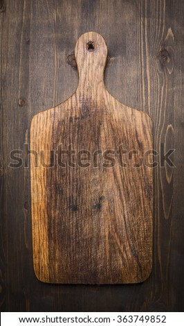 old vintage wooden cutting board  on wooden rustic background top view close up - stock photo