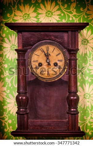 Old vintage wooden wall clock hanging on green wall - stock photo