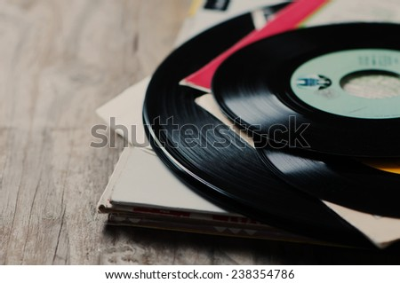 old vinyl record on the wooden table, selective focus - stock photo