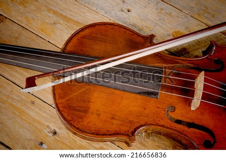 Old violin and arch on a wooden background - stock photo