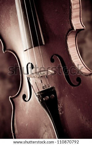 Old violin on a dark background - stock photo