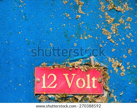 old 12 volt signage on grunge metal - stock photo
