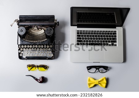 Old vs new; Modern silver laptop and an old vintage black typewriter - stock photo