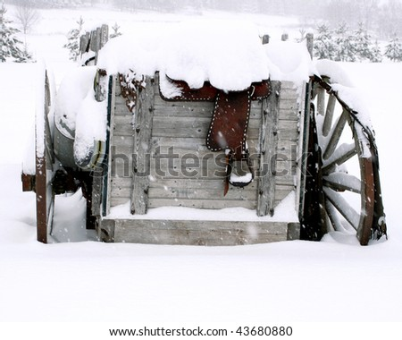 Old wagon in the snow with various western items on it - stock photo