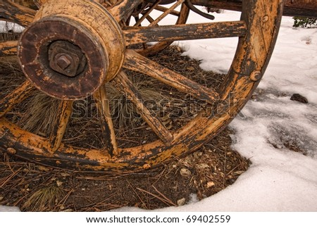 old wagon wheel in snow; part of western series in portfolio - stock photo