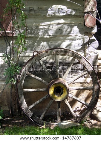 Old wagon wheel outside vintage settler cabin