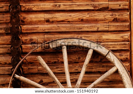 old wagon wheel side by wooden wall - stock photo
