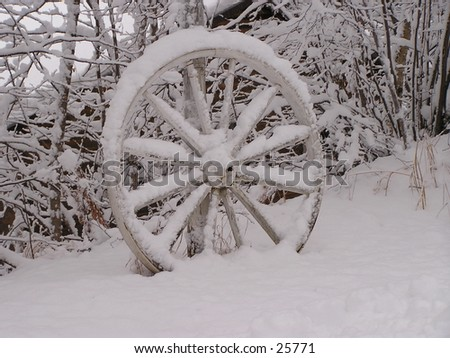 old wagon wheel under snow - first november snow 2004 in North Laurentian, Quebec - stock photo