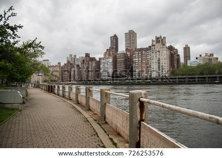 Old walkway next to river with dark cloudy sky