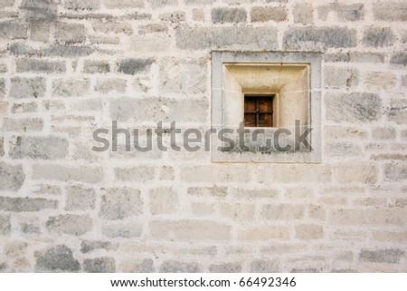 Old wall of sandstone with little barred window closed - detail of building in Mallorca. Texture of stone. - stock photo