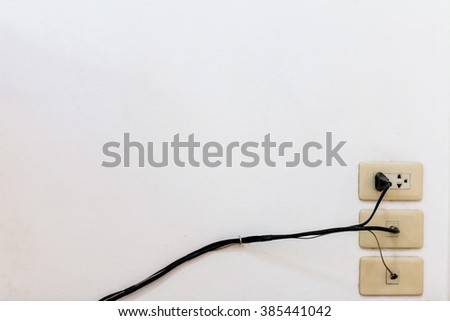 Old wall outlet old. Plugged power cord in wall socket. - stock photo