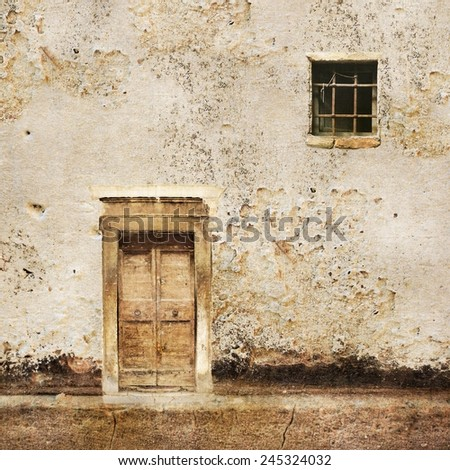 Old wall with wooden door and small window - stock photo