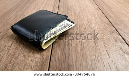 Old wallet with dollar banknotes on wooden background - stock photo