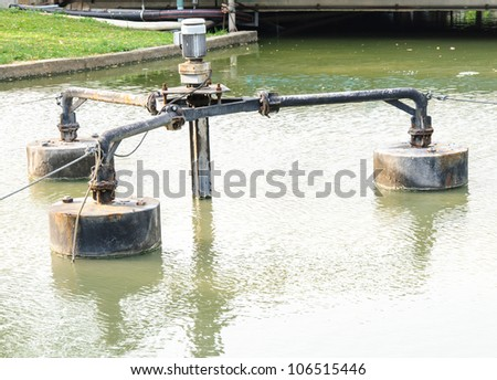 Old water pump in the reservoir of university. - stock photo