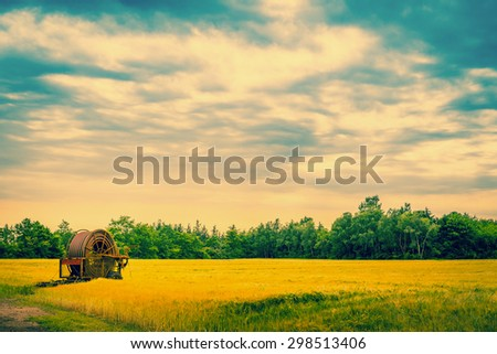 Old water pump on a field in cloudy weather - stock photo