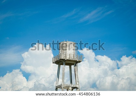 Old water tank in countryside under cloudy sky in summer - stock photo