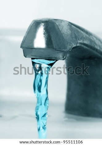 old water tap with running blue water - stock photo