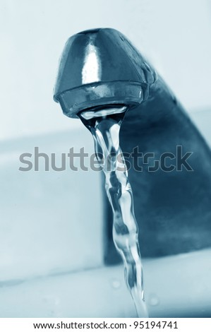 old water tap with running water - stock photo