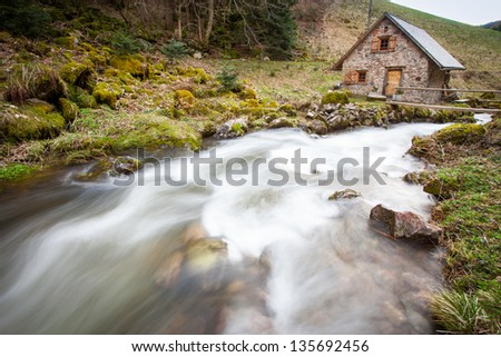 old watermill house near a river in black forest - stock photo