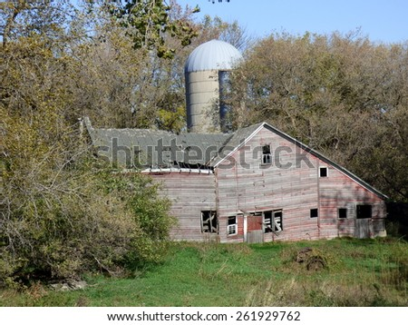 old weathered abandoned farm building red barn and silo - stock photo