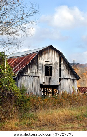 Old weathered and worn wooden barn stands surrounded by Autumn foliage.  Ozark Mountains stand in background. - stock photo