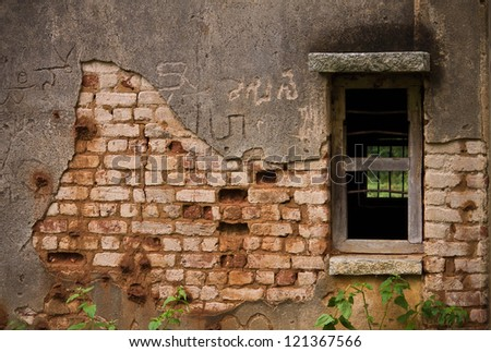 old weathered cement wall exposing broken bricks background with old window - stock photo