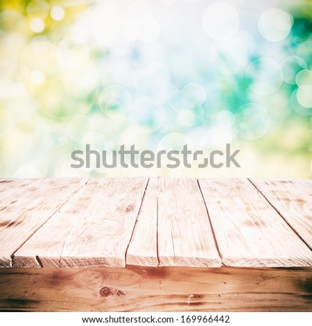 Old weathered cracked wooden table in a sunny summer garden with a high key background, low angle with space for product placement - stock photo
