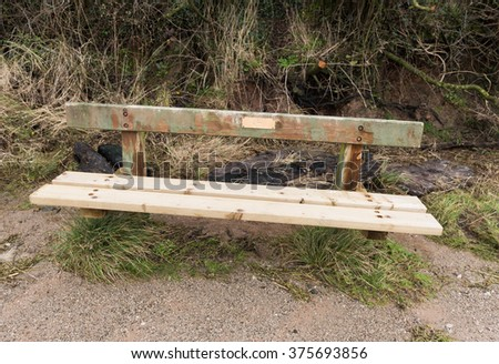 old weathered distressed wooden bench with earthy colours - stock photo