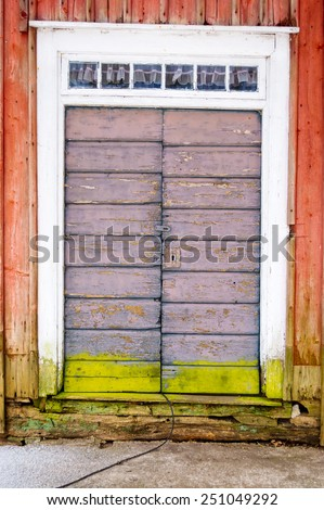 Old weathered door with fine colors and lock. Green line of moss on lower part of door and red paint on surrounding walls. Small windows over door. - stock photo