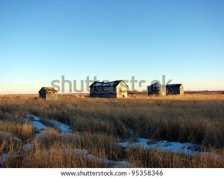 old weathered farm building at sunset - stock photo