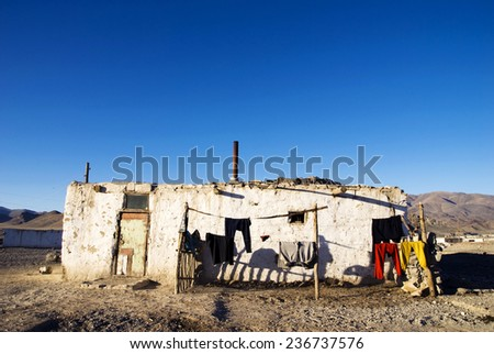 Old weathered house with mountain range at the background. - stock photo
