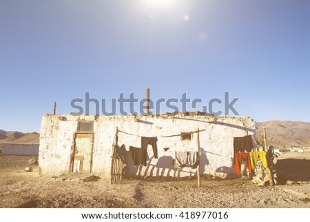 Old weathered house with mountain range at the background.