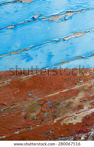 Old weathered orange and blue hull - stock photo