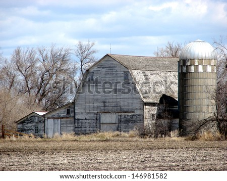 old weathered rural buildings gray barn with silo - stock photo
