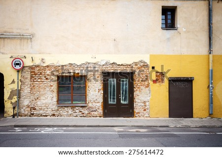 Old weathered street wall with some windows and doors - stock photo